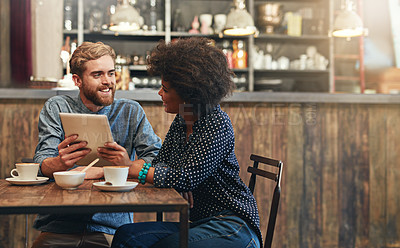 Buy stock photo Shot of a young couple using a digital tablet together on a coffee date