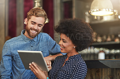 Buy stock photo Shot of young coffee shop workers using a digital tablet together