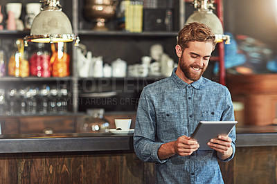 Buy stock photo Shot of a young man using a digital tablet in a cafe