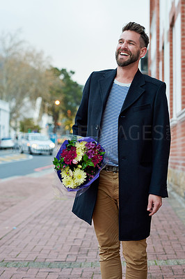 Buy stock photo Cropped shot of a handsome young man walking through the city with a bunch of flowers in hand
