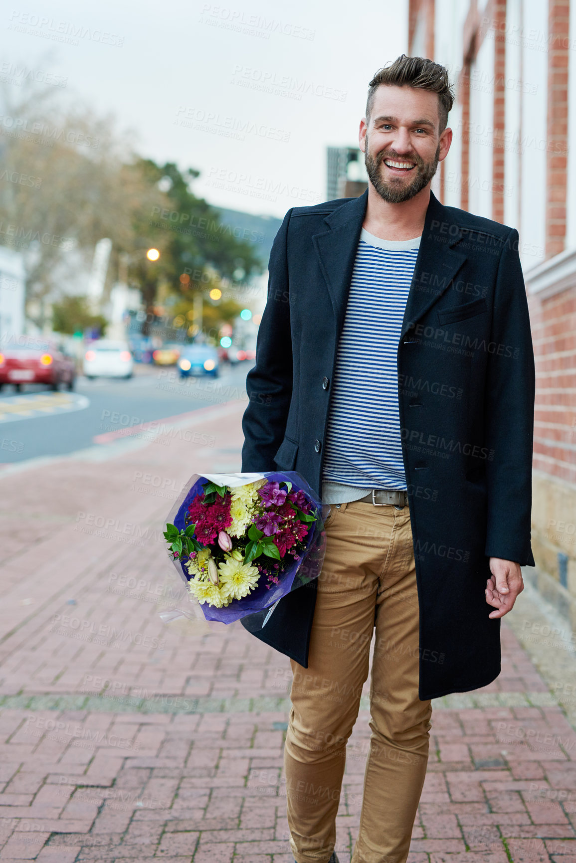Buy stock photo Portrait of a handsome young man walking through the city with a bunch of flowers in hand