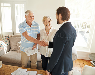 Buy stock photo Shot of a senior couple shaking hands with their financial consultant in their living room