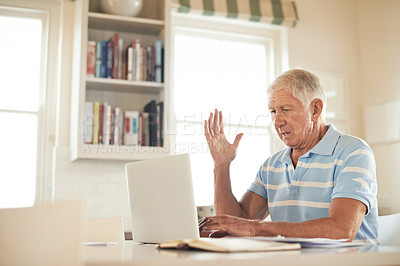 Buy stock photo Shot of a senior man looking stressed while using a laptop in his kitchen
