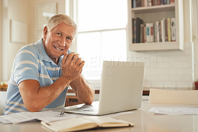 Buy stock photo Portrait of a smiling senior man doing the household finances on a laptop in his kitchen