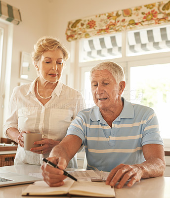 Buy stock photo Shot of a senior couple doing their household finances on a laptop in his kitchen