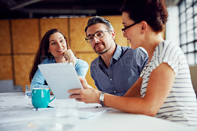 Buy stock photo Shot of a group of designers using a digital tablet in their meeting