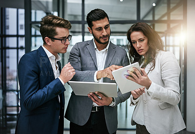 Buy stock photo Shot of a group of colleagues using a digital tablet together at work