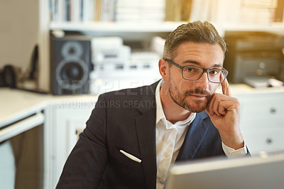 Buy stock photo Portrait of a businessman working at his computer in an office