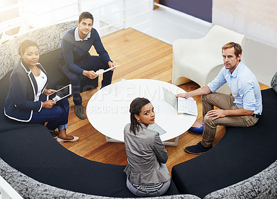 Buy stock photo High angle portrait of a group of colleagues having a meeting around a table in a modern office