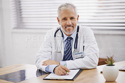 Buy stock photo Portrait of a mature male doctor sitting at his desk