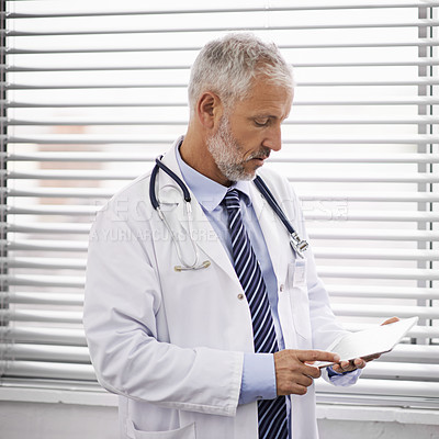 Buy stock photo Cropped shot of a mature male doctor using a digital tablet