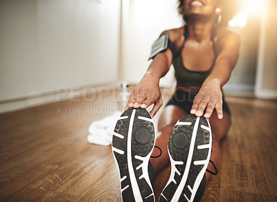 Buy stock photo Shot of a young woman doing stretching exercises at home
