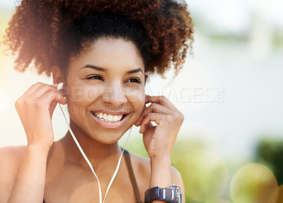 Buy stock photo Cropped shot of a young woman inserting her earphones before a run
