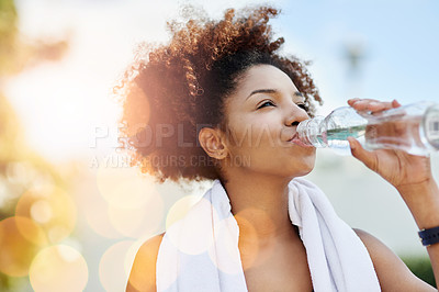Buy stock photo Cropped shot of a young woman enjoying a bottle of water while out for a run