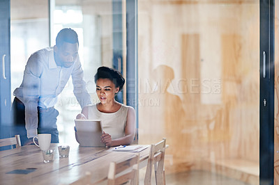 Buy stock photo Shot of two colleagues using a digital tablet together in an office