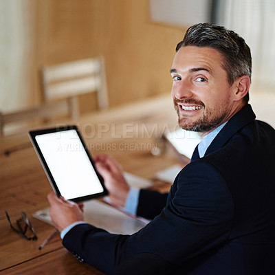 Buy stock photo Portrait of a smiling executive using a digital tablet while sitting alone at a table in an office