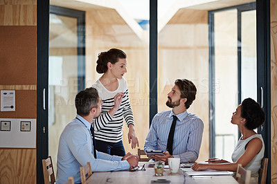 Buy stock photo Portrait of a group of colleagues talking together around a table in an office