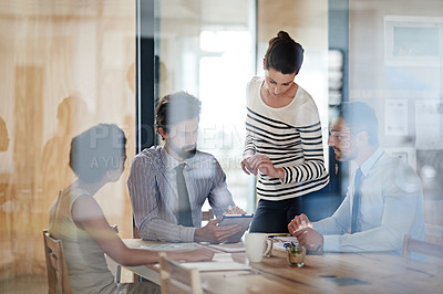 Buy stock photo Shot of a group of colleagues using a digital tablet together while working around a table in an office