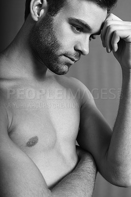 Buy stock photo Black and white shot of a handsome and shirtless young man looking pensive