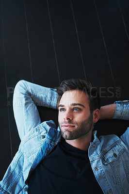 Buy stock photo Shot of a handsome young man lying on the floor and looking pensive