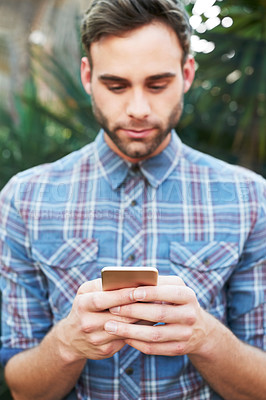 Buy stock photo Cropped shot of a handsome young man sending a text while standing outside
