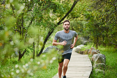 Buy stock photo Shot of a young man out for a run in the park