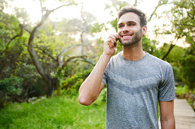 Buy stock photo Cropped shot of a young man talking on a cellphone in a park