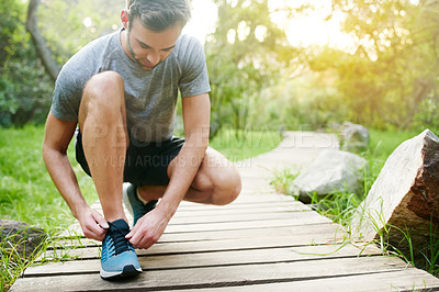 Buy stock photo Shot of a young man tying his laces while out for a run in the park