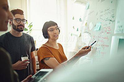 Buy stock photo Shot of a group of young designers working on a whiteboard