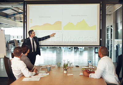 Buy stock photo Shot of an executive giving a presentation on a projection screen to a group of colleagues in a boardroom