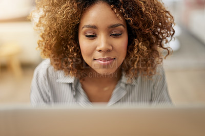 Buy stock photo Cropped shot of a young woman working on her laptop