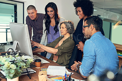 Buy stock photo Cropped shot of a group of businesspeople discussing something on a computer in an office