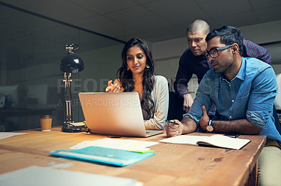 Buy stock photo Cropped shot of a group of businesspeople working late on a laptop in an office