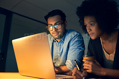 Buy stock photo Cropped shot of two colleagues working late on a laptop in an office