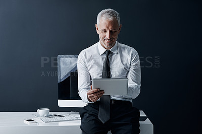 Buy stock photo Cropped shot of a mature businessman working on his tablet