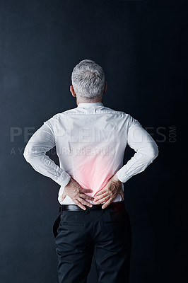 Buy stock photo Rearview shot of a mature businessman holding his back in pain
