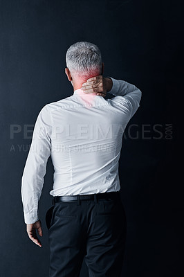 Buy stock photo Rearview shot of a mature businessman holding his neck in pain