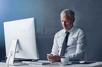 Buy stock photo Cropped shot of a mature businessman sending a text while working on his computer