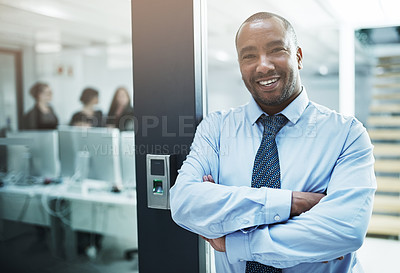 Buy stock photo Portrait of a young businessman standing with her arms crossed in an office doorway