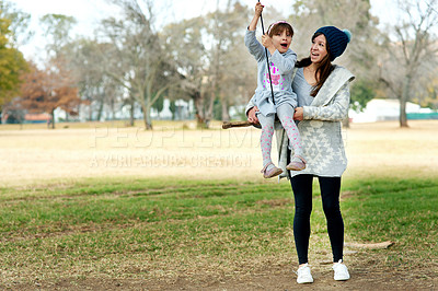 Buy stock photo Shot of a mother pushing her daughter on a swing at the park