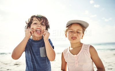 Buy stock photo Portrait of two young siblings pulling funny faces while playing on the beach
