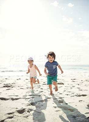 Buy stock photo Portrait of two young siblings running on the beach