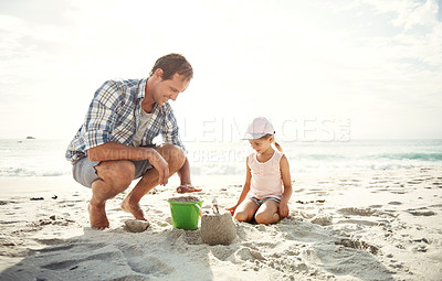 Buy stock photo Shot of a father building a sandcastle on the beach with his young daughter