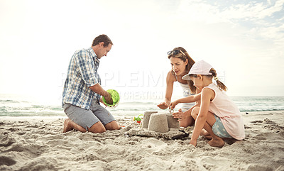 Buy stock photo Shot of a mother and father building a sandcastle on the beach with their young daughter