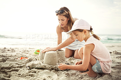 Buy stock photo Shot of a mother building a sandcastle on the beach with her little girl