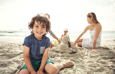 Buy stock photo Portrait of a little boy sitting on the beach with his family