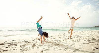 Buy stock photo Shot of two excited young children doing cartwheels on the beach