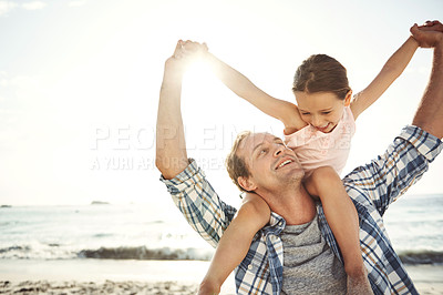 Buy stock photo Shot of a father carrying his little girl on his shoulders at the beach