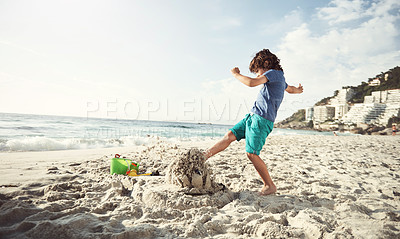 Buy stock photo Shot of a little boy kicking over a sandcastle at the beach