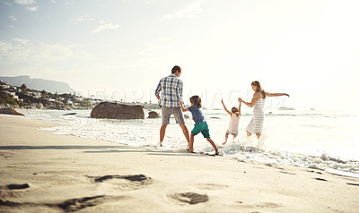 Buy stock photo Shot of a happy young family splashing in the waves at the beach
